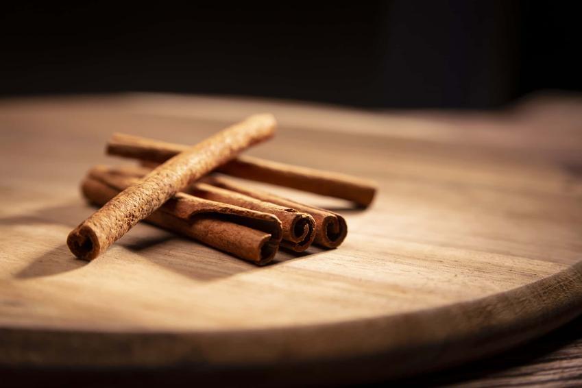Laski cynamonu na drewnianej desce, a także właściwości cynamonu i jego wpływ na zdrowie
