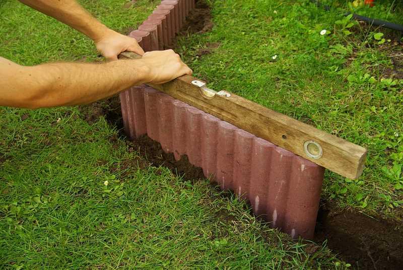 Niska palisada ogrodowa betonowa wokół ogrodu ozdobnego, a także inne palisady ogrodowe betonowe, ich cena, wymiary oraz montaż
